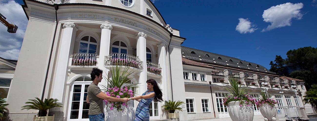 Couple hand in hand in front of the Kurhaus Merano