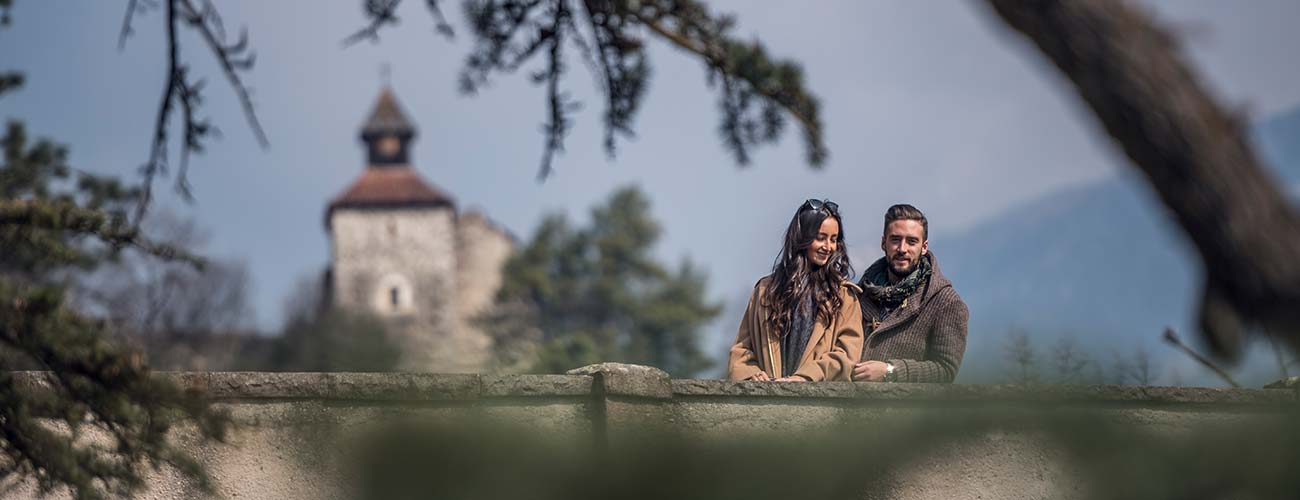 A couple on a bridge overlooking the city of Merano