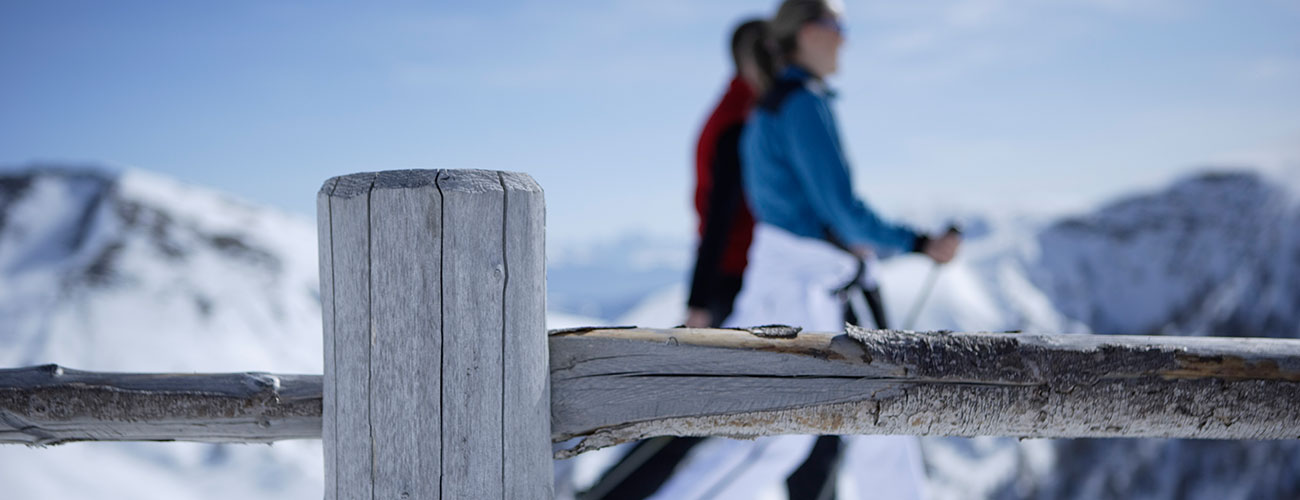 Wooden fences and two people walking in winter in the mountains